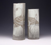 Tall Vases with Herons Description: Thick coils of stoneware clay are rolled opened from the inside using dowels, resulting in free but structured forms. White stoneware slip is loosely applied, then carved through with illustrations. Inspired by the themes and techniques of traditional Korean pottery, applied to modern forms. Dimensions: H:15.00 x W:5.00 x D:5.00 Inches