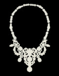 Iconic Decorative Necklace Description: Necklace hand-pierced from 20g brass then powder coated cream. Necklace design inspired by images found in historical jewelry. Dimensions: H:12.00 x W:6.50 x D:0.03 Inches