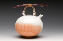 Tangerina Julius Description: Wheel thrown Porcelain Teapot. Dyed Reed Handle. Diminutive Series Dimensions: H:5.00 x W:7.00 x D:4.00 Inches