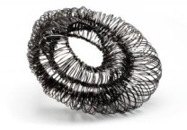 WYRED Description: One of a Kind Brooch - Using threads of wire I am creating the illusion of inside outside undulating forms. - Steel & sterling silver Dimensions: H:4.30 x W:3.80 x D:2.00 Inches