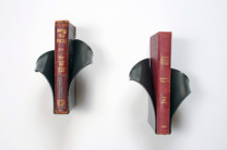 Book Sconces Description: An individual book display for a rare or favorite book, hot worked steel with transparent black powder coat finish. Dimensions: H:7.00 x W:6.00 x D:7.00 Inches