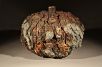 """Oval Lava Bottle Description: the lava pieces are constructed from hundreds of """"raw bits"""" attached one at a time to a preformed shape... the piece is meant to be built or """"grow"""" in an organic manner disguising it's hand made origins. the colors are from ash accumulation in the wood kiln. Dimensions: H:14.00 x W:12.00 x D:10.00 Inches"""