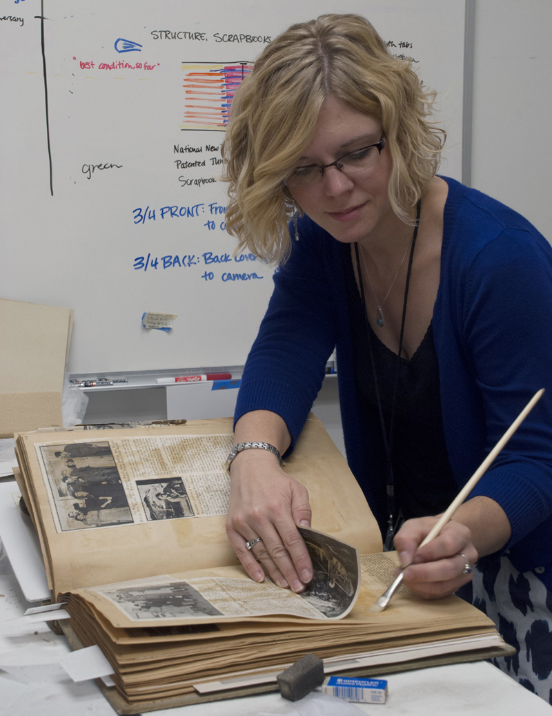 Intern Sarah Casto applies wheat starch paste to readhere a loose clipping inside one of the Macbeth Gallery Scrapbooks. Photo: Sarah Casto.
