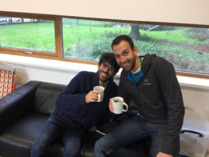 Two men sitting on couch with mugs.