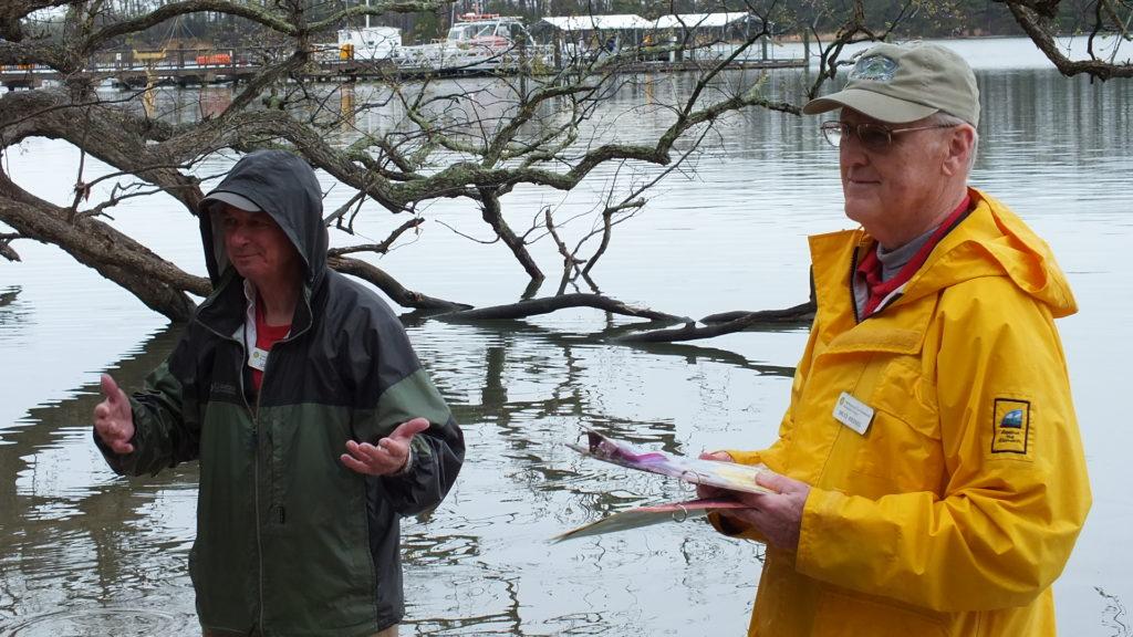 Two men in jackets beside river.