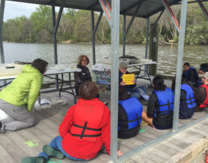 Seated man talks to kids in life jackets on floating dock.