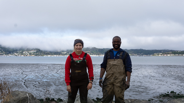 Two people standing in front of a mudflat