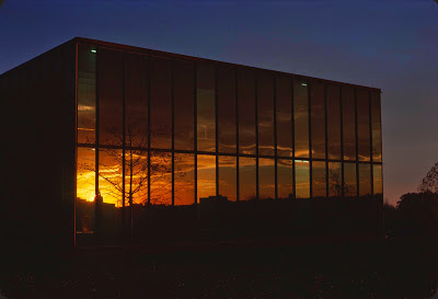 Reflection on the outside west wall of the U-M Computing Center Building at sunset