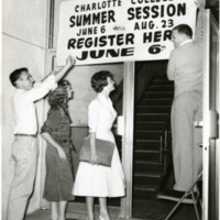 Students post a sign announcing Charlotte College summer classes, 1957