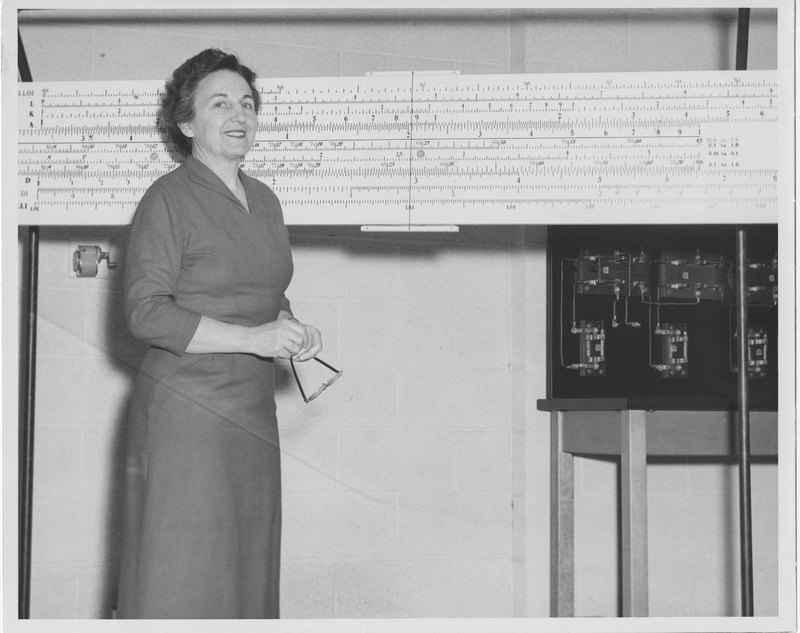 Bonnie Cone stands in front of a slide rule, January 27, 1958
