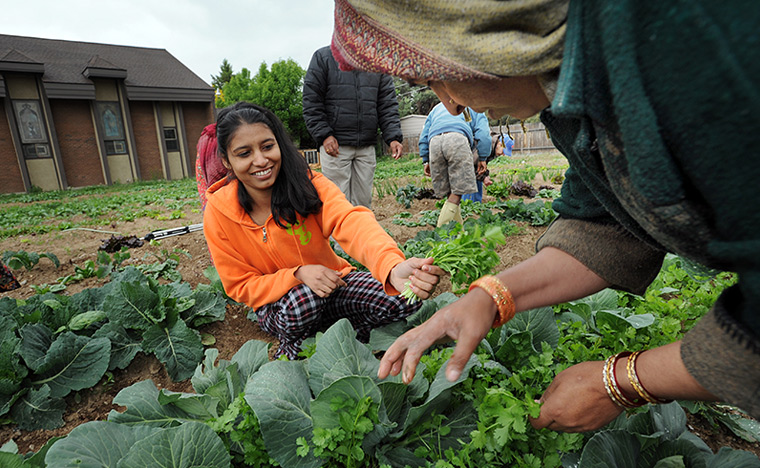 Small-scale wind production. Small plots for urban farming. Small mixed-use infill projects. Small walkable blocks. Small neighborhood schools. Pictured: Puspa Lal Regmi of Boise tends a small urban farm.
