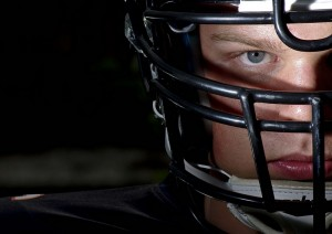 Football helmets and padding.  Why is football more dangerous than rugby?  Because the equipment that protects players from routine bruises also allows harder hits. Modern helmets allow players to spear with their heads, causing concussions.