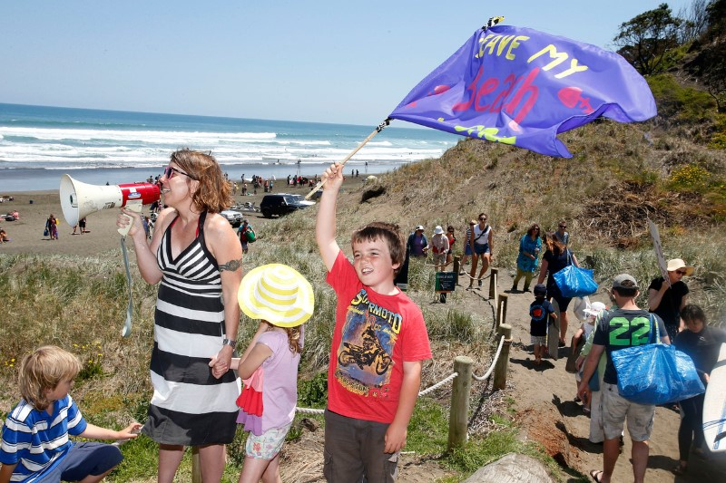 Banners on the beach. Greenpeace NZ Programme Director Carmen Gravatt rallies the crowd opposing deep sea oil drilling in New Zealand waters at the 'banners on the beach' event at Muriwai. Similar events are on about 45 North Island west coast beaches and others are happening in solidarity on the East Coast and in the South Island. They have been organised in support of the Oil Free Seas Flotilla which is protesting where oil giant Anadarko intends to start drilling. The site is over 100 nautical miles off the west coast of New Zealand, and in waters around a kilometre and a half deep.  Greenpeace/Nigel Marple