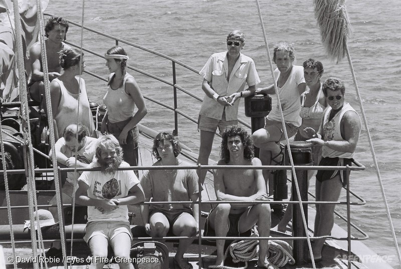 Rainbow Warrior crew in 1985. Clockwise from top centre, Lloyd Anderson (in headband and glasses), engineer Henk Haazen, deckhand Bunny McDiarmid, captain Peter Willcox, mate Martini Gotje, deckhand Grace O'Sullivan, mate Bene Hoffmann, engineer Davey Edward, cook Nathalie Mestre, engineer Hanne Sorensen, deckhand and doctor Andy Biedermann.