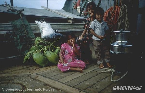 Woman and two children on deck of RW, pans and fruit by their side. Operation Exodus Rongelap. Health of many adults and children has suffered as a result of fallout from US nuclear tests. Crew Rainbow Warrior took adults, children and 100 tonnes of belongings onboard and ferries them to island of Mejato. Note: last photos of Fernando Pereira. (The Greenpeace story book page 111 similar)05/14/1985 © Greenpeace / Fernando Pereira
