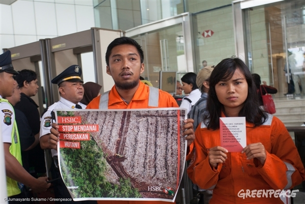 Adi Prabowo (left) and Larasati Mido Matovani (right) carrying banner during a protest at HSBC headquarter in Jakarta