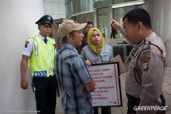 Police debates with Greenpeace forest campaigners Yuyun Indradi (2nd left) and Annisa Rahmawati (2nd right) during a protest at HSBC headquarter in Jakarta