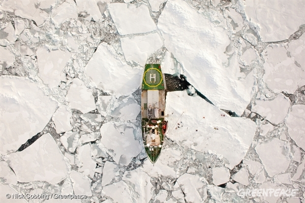 The Arctic Sunrise, photographed above from a helicopter, moored to an ice floe by stakes hammered into the ice. Tiny figures can be seen working on the floe, drilling holes into the ice. The Arctic Sunrise is one of three Greenpeace ships seeking to bring attention to the effect of climate change and Save the Arctic.