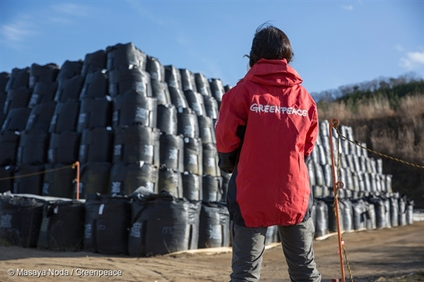 Greenpeace radiation survey team member Ai Kashiwagi (Japan) standing in front of nuclear waste storage area in Iitate Village, Fukushima Prefecture.