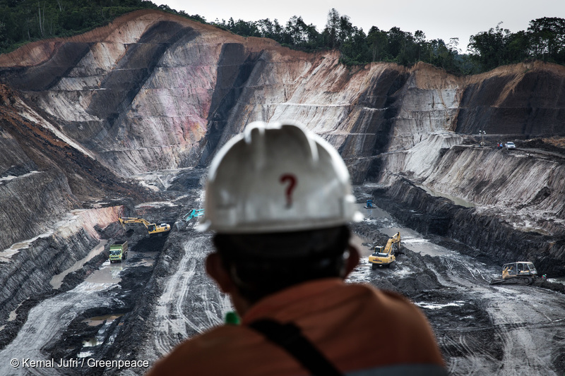 A worker on a break looks over an open-pit coal mining concession in Makroman, East Kalimantan, Indonesian Borneo. At its most destructive pattern of operation, coal extraction transforms mountain tops into giant holes using explosives, the cheapest way employed by many coal mining companies in Indonesia.