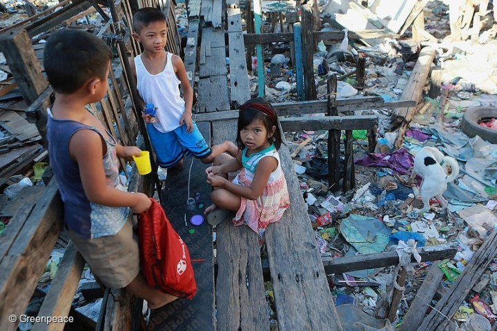 Children play on a trash-filled river in Barangay Bagumbayan North in Navotas City, Philippines.