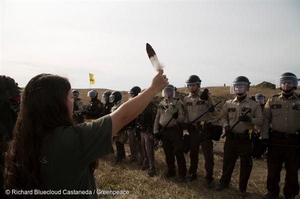다코타 송유관 건설에 대항하는 물 지킴이들(Water Protectors)이 스탠딩 락 근처 캠프에 줄지어 서있는 경찰들 앞에서 독수리 깃털을 손에 쥔 채 시위하고 있습니다.