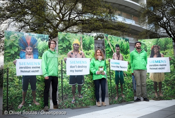 """Greenpeace activists protest in front of the German Siemens headquarter in Munich.  The activists hold photos of Indigenous People and signs reading """"Save the Tapajós"""", """"Don't destroy my home"""" and """"No dams in the Amazon"""" to raise awareness and inform Siemens employees and the public about the company's plan to get involved in the construction of a new mega dam in Brazil. 13 Apr, 2016  © Oliver Soulas / Greenpeace"""