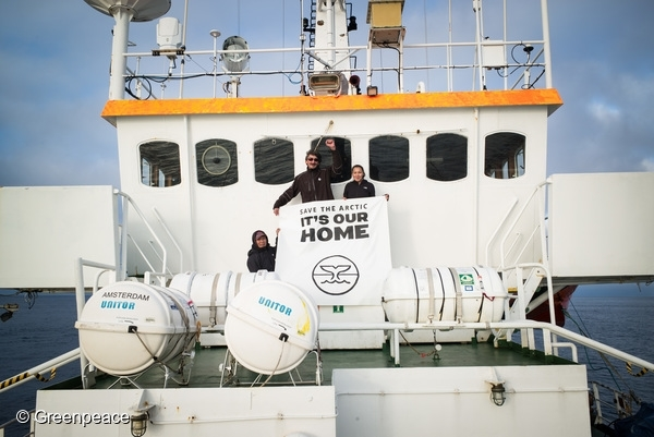 Mayor of Clyde River, James Qillaq (L), former mayor of Clyde River, Jerry Natanine and Jerry's daughter, Clara hold an anti-seismic blasting banner, on the bow of the Arctic Sunrise, in Baffin Bay. 13 Aug, 2016  © Greenpeace