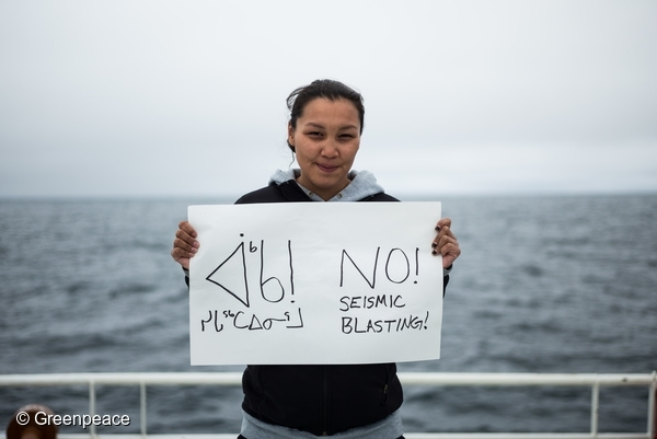 Resident of Clyde River, Clara Natanine stands on the deck of the Arctic Sunrise with an anti-seismic blasting sign that she made herself. 11 Aug, 2016  © Greenpeace