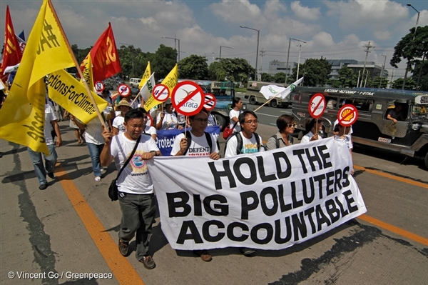 "Protestors march the streets holding a banner reading, ""Hold the Big Polluters Accountable"" in Quezon City, Philippines. They are calling for an investigation into the responsibility of big fossil fuel companies for fuelling catastrophic climate change that is resulting in human rights violations."
