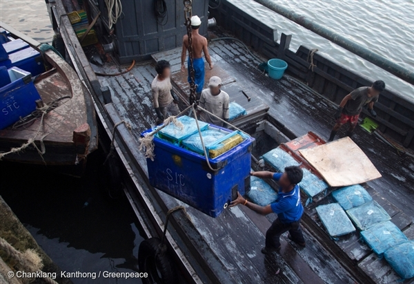 Port workers unload fish from a vessel docked at the public fishing port in Ranong, southern Thailand.