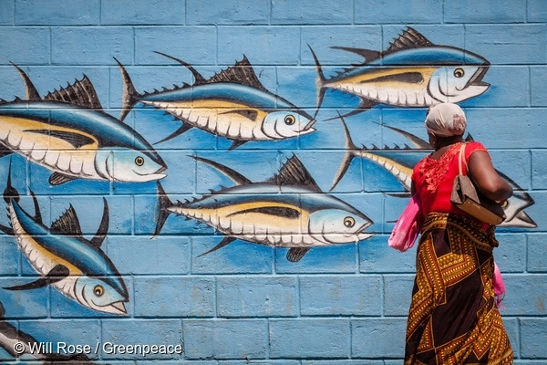 A woman walks past a wall painted with tuna fish outside the port in Diego Suarez. 15 Apr, 2016  © Will Rose / Greenpeace
