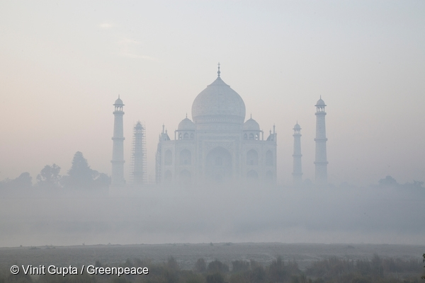 A hazy morning has made  the Taj Mahal look like a dark silhouette against a foggy foreground.