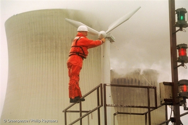 A Greenpeace activist erects a wind powered turbine in front of the Doel nuclear power plant in protest against energy discrimination by the Belgian government in favour of electricity generated by nuclear power over safe and inexpensive renewable wind energy. 1 July, 2002 © Greenpeace / Philip Reynaers