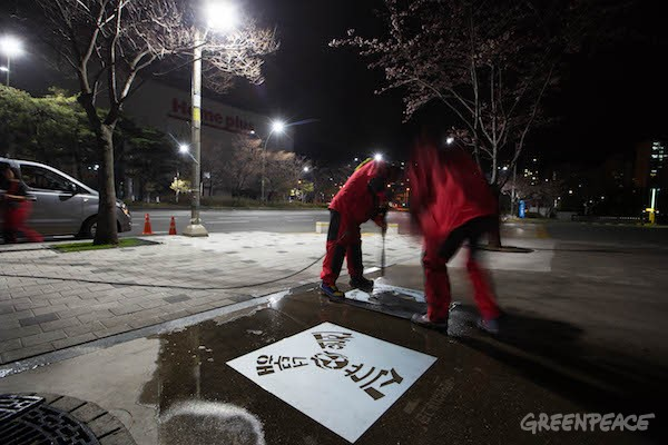 "Greenpeace activists use a high pressure cold water cleaner to create ""Reverse Graffiti"" on the streets of Busan, Korea. There are four different types of a graffiti message. The wordings are all playful parodies of widely used word-plays in Korean. Added with the pictorial symbols, the messages say, ""New Nuclear Plants are just too much, Fukushima-Chernobyl-Busan, Nuclear is a disease and the only cure is your vote, Tell them to stop the nuclear winds"". The graffiti action aims to create a playful and direct dialogue with the citizens of Busan. As the general election is coming in April, through this action, Greenpeace intend to inform what the Busan citizens can do as a voter. The Korean government is planning to build two additional reactors at the Kori Nuclear Power Complex, the world's largest nuclear power plants site, located between Busan and Ulsan. The plant already has six reactors and there are around 3.4 million people living within the 30km zone around the plant."