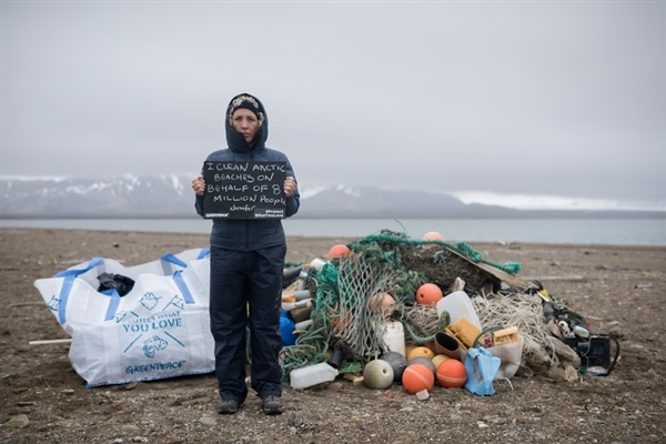 Greenpeace International Executive Director Jennifer Morgan holding up a message to the Norwegian government in front of a pile of garbage collected from a beach at Sarstangen on Prince Carls Forland, the west coast of Svalbard. 25 Jun, 2016 © Christian Åslund / Greenpeace