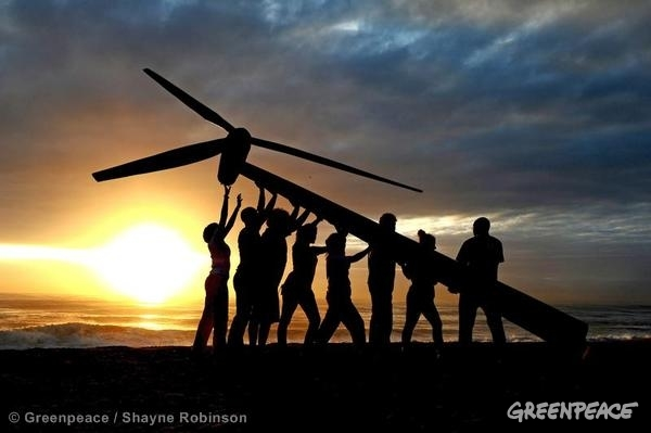Greenpeace and Tcktcktck volunteers raise a wind turbine on the beach at dawn in Durban, South Africa.