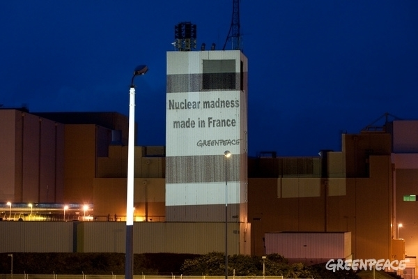 Greenpeace activists beam 'Nuclear madness made in France' onto the AREVA reprocessing facility at La Hague  © Greenpeace / Pierre Gleizes