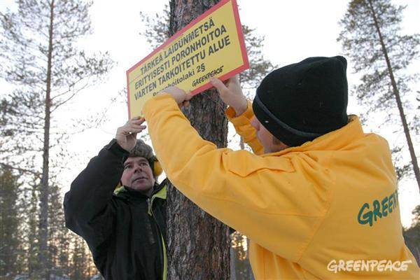 Saami Reindeer herder with Greenpeace activist in Finland's forest