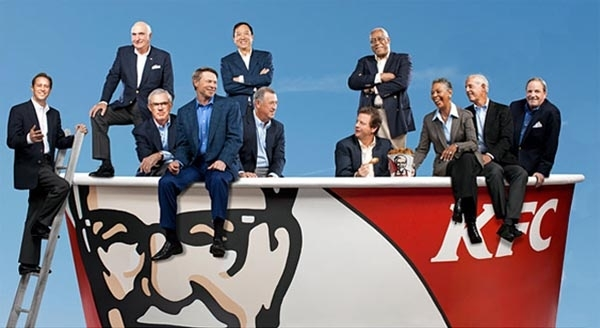 KFC board members pose playfully on top of giant KFC bucket.