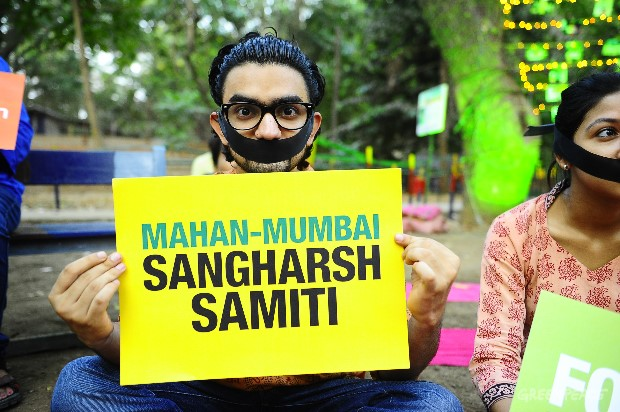 A volunteer with a black band around his mouth participates in a solidarity event supporting Mahan. The people of Mumbai stand with Mahan Sangharsh Samiti in the fight to save Mahan.