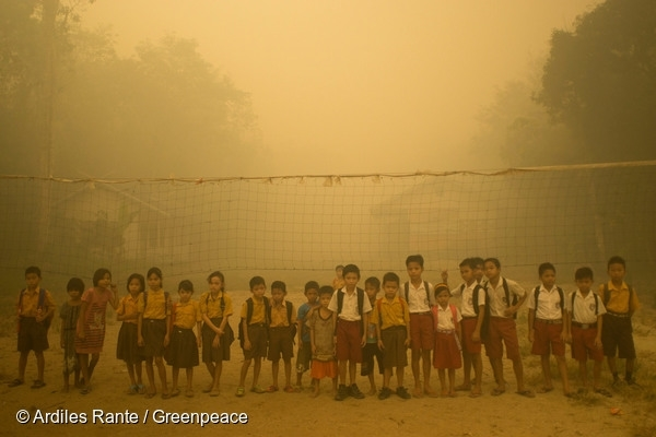 Children play without wearing any protection while the air is engulfed with thick haze from the forest fires at Sei Ahass village, in Central Kalimantan province on Borneo island, Indonesia