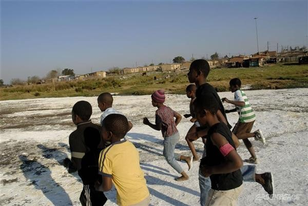 Children from the local community of Maguqa play on a field of white salt precipitate from the AMD (acid mine drainage). The pollution is caused by the water containing a mixture of AMD coming from abandoned local coal mines,  a ticking time-bomb for the environment. The water draining from the mines is also filled with sulphate salts, heavy metals and carcinogenic  substances like benzene and toluene.