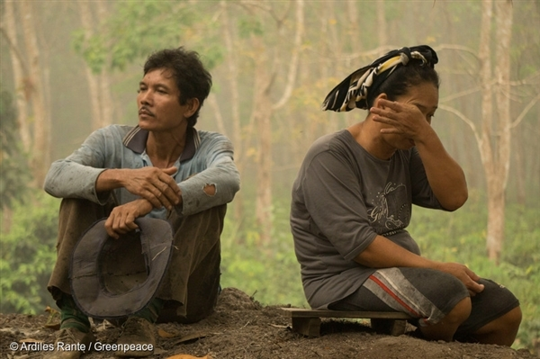 A couple guard their rubber tree plantation to make sure it doesn't catch fire