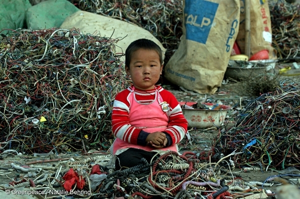 A small Chinese child sitting among cables and e-waste, Guiyu, China. Much of modern electronic equipment contains toxic ingredients