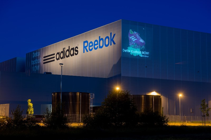 Greenpeace Germany activists project their message at an adidas distribution centre.