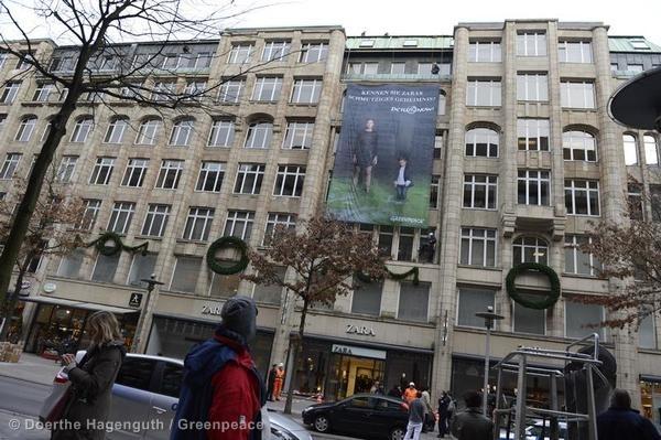 """Escaladores cuelgan una pancarta enorme en frente de una tienda ZARA en Hamburgo donde se pregunta a los transeúntes: """"¿Cónoces el sucio secreto de ZARA?"""