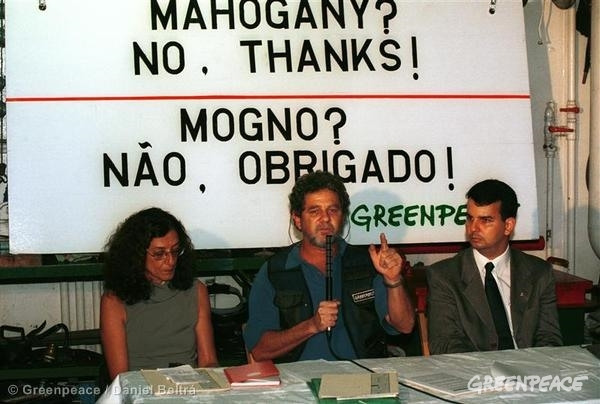 "At a Greenpeace press conference in Brazil, Paulo Adario is speaking into a microphone and is seated in between two other people at a desk. Behind them is a large sign written in Portuguese and English: ""Mahogany? No. Thanks!"""