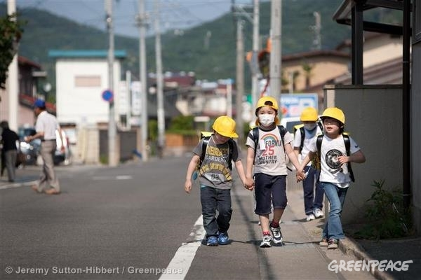 Children walk along a road which had earlier been assessed by a Greenpeace team for radioactive contamination. The team found the road to contain high, unsafe levels of contamination. The city of Fukushima has been contaminated by radioactive fallout from the ongoing crisis at the Fukushima Daiichi nuclear plant. Within the city, local authorities are now undertaking a clean up operation of soil from school and nursery school playgrounds. 06/07/2011 © Jeremy Sutton-Hibbert / Greenpeace