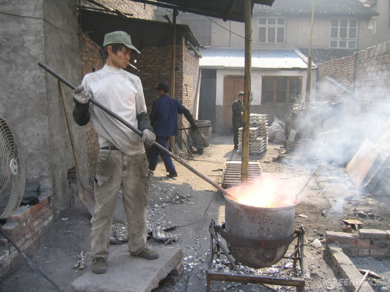 Chineseman smelts computer parts in the open air to extract metals. Open air burning of computer waste releases large amounts of toxic fumes. (© Greenpeace/Lai Yun)